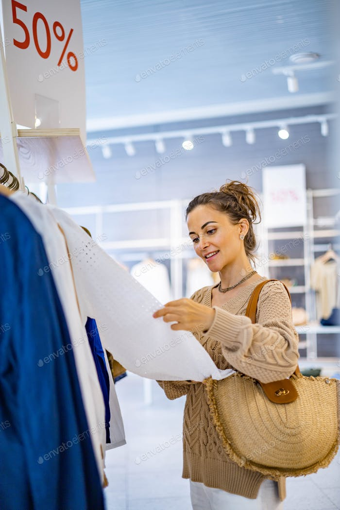 Happy woman buyer relaxing enjoying 50 percent sale at fashion boutique choosing clothes