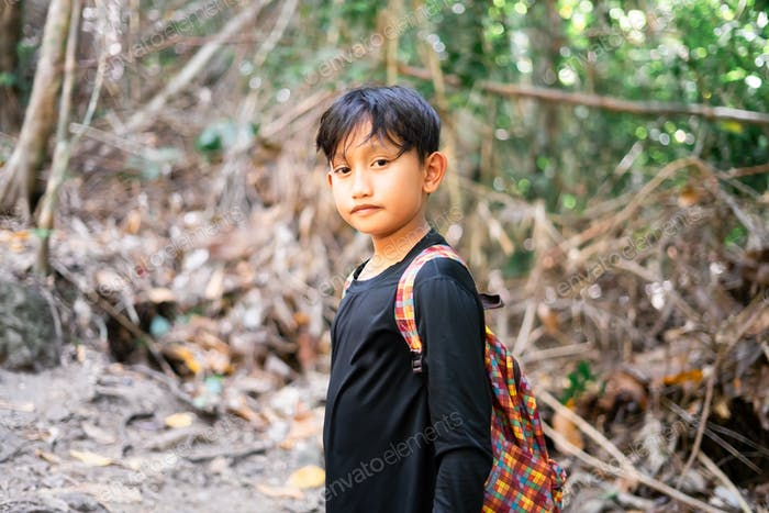 portrait of Asian boy in the jungle. Active kids concept.