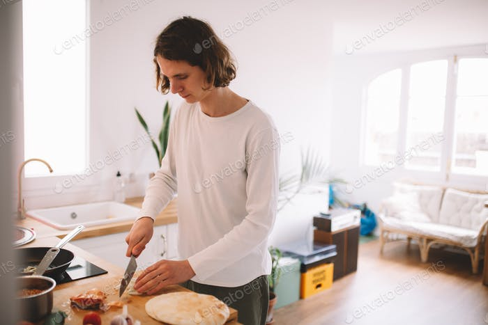 young hipster millenial boy cooking vegeterian vegan falafel on bright sunny white traditional woode