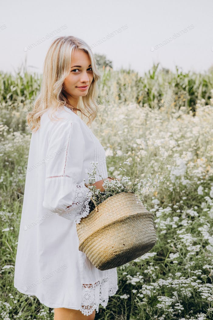 a girl in a white sundress walks in the meadow