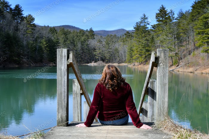 Active Baby Boomer Gen-X middle aged woman sitting on a platform by a lake looking at the mountains,