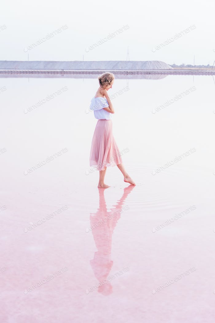 A young beautiful woman in a long tender pink skirt is standing barefoot in a pastel pink salt lake