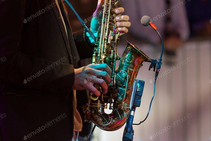 Man playing saxophone, hands with instrument in frame