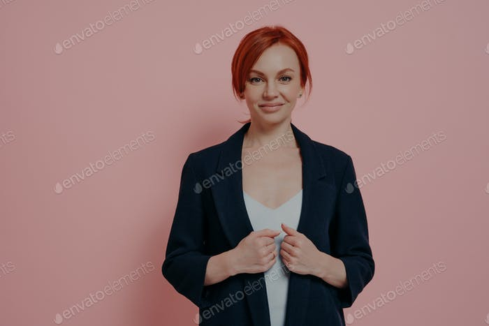 Beautiful stylish redhead female adjusting formal navy jacket isolated over pink background