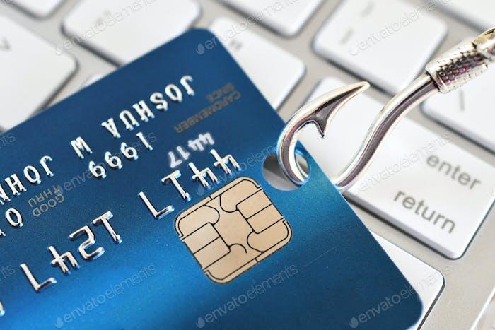 concepto de robo de identidad fraudulento fraude phishing - tarjeta de crédito en el anzuelo de pesca en el teclado blanco de la computadora