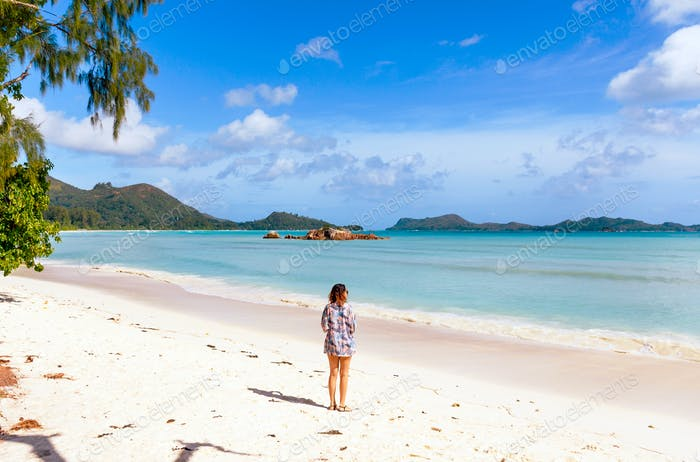 Rear view of woman standing on tropical sandy beach, summer, one person.