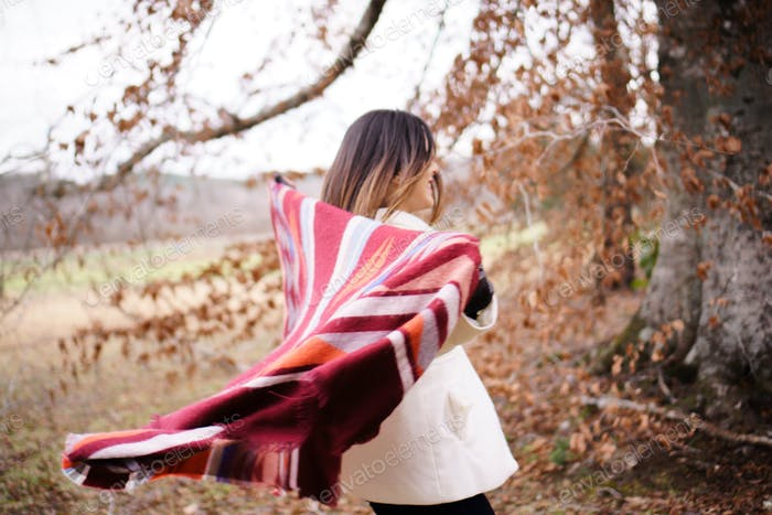 Woman with blanket in fall