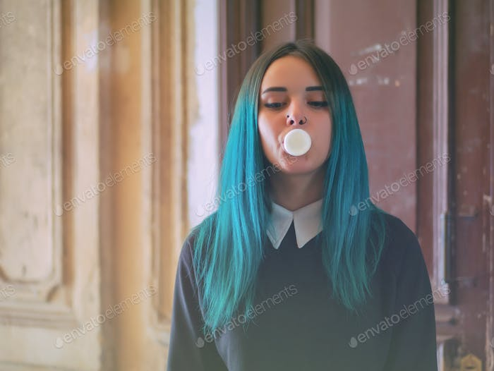 Portrait of Young girl with blue hair blowing bubble