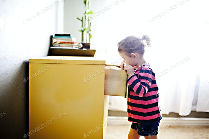 Girl looking in a yellow dresser for clothes