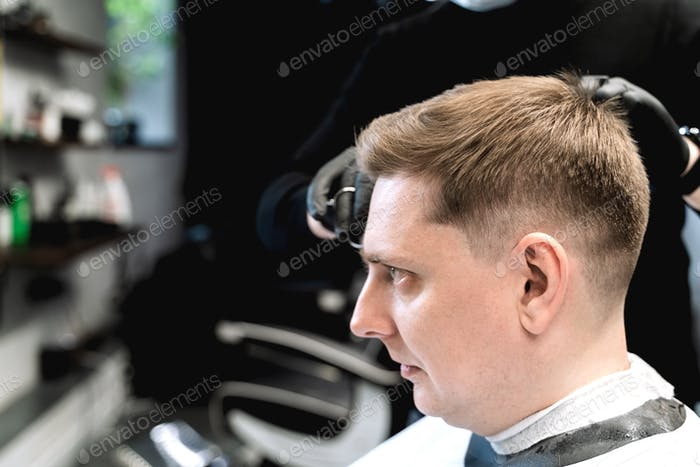 Visit to barbershop. Stylish man makes fashionable haircut. Barber,hairdresser,stylist with scissors