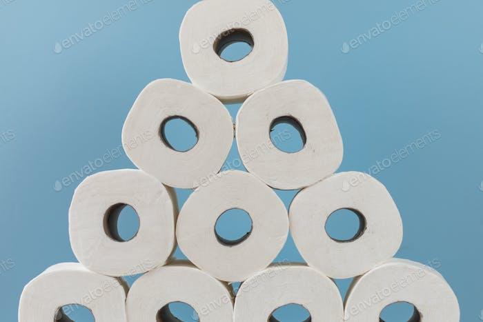 Stapel von Rollen Toilettenpapier auf blauem Hintergrund