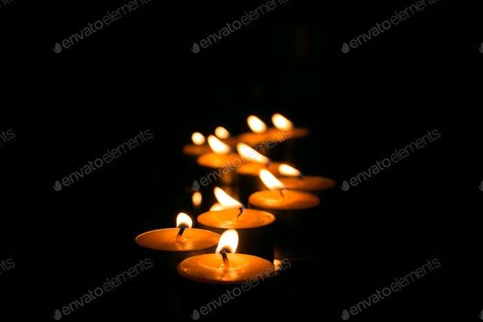 Several small candles in ziz zag shape despair in the in the dark