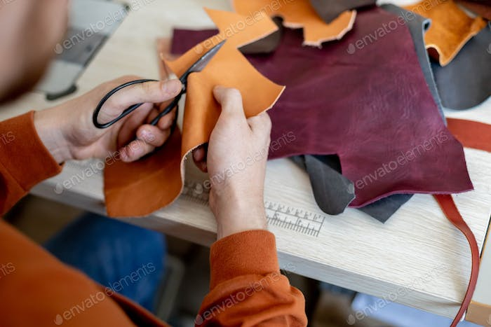 Craftsman cutting natural material use scissors. Working process at leather workshop