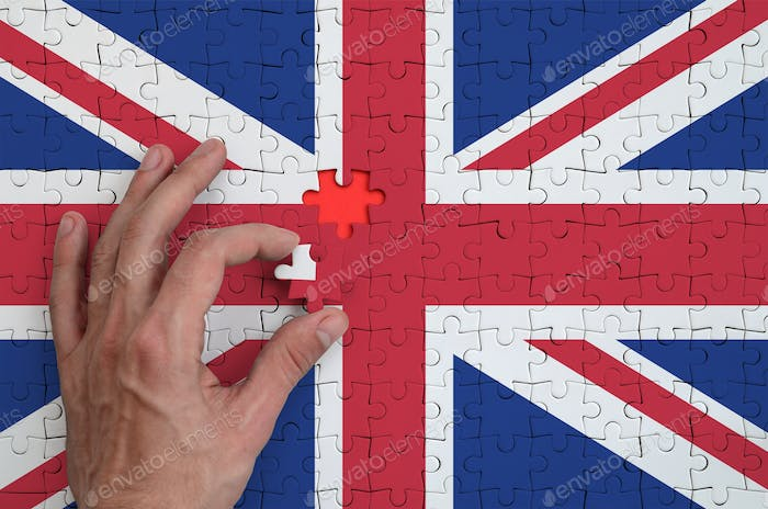 Great britain flag  is depicted on a puzzle, which the man's hand completes to fold.