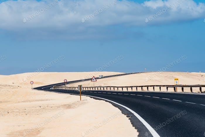 Vista panorámica de la carretera a través de dunas de arena contra el cielo. Corralejo, Fuerteventura, Canarias