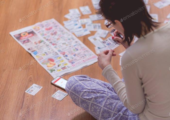 Frau zu Hause Clipping Coupons aus Nachrichtenzeitung auf dem Boden