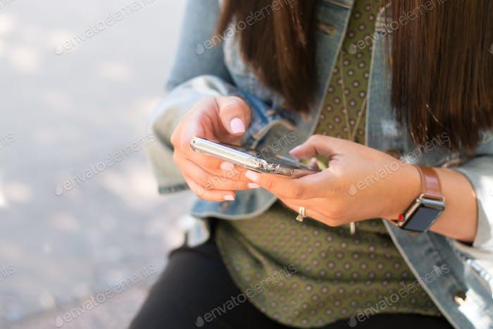 Young Latina woman texting on phone