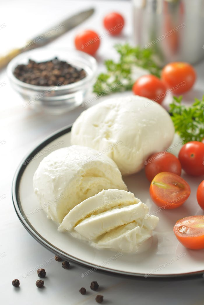 Mozzarella cheese and cherry tomatoes with spices. Homemade mozzarella cheese, isolated.