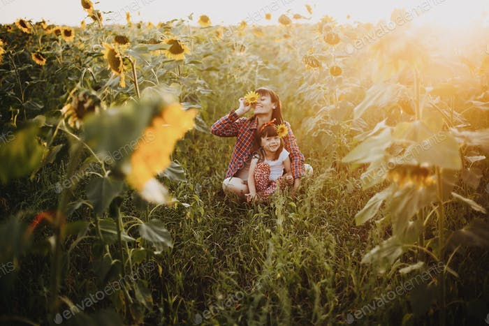 Mum and babygirl having fun in the field of sunflowers