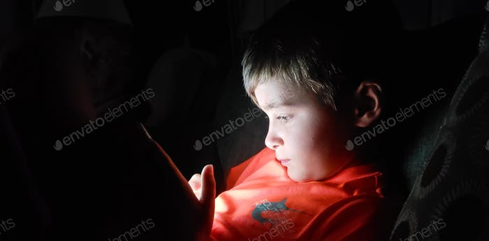 Little boy focused on his iPad at night with lighted face and learning alot of cool stuff ....