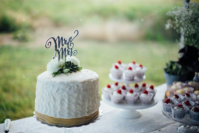 Ein Mr. and Ms Zeichen sitzt auf einer Hochzeitstorte mit anderen Wüsten im Hintergrund und grünem Gras