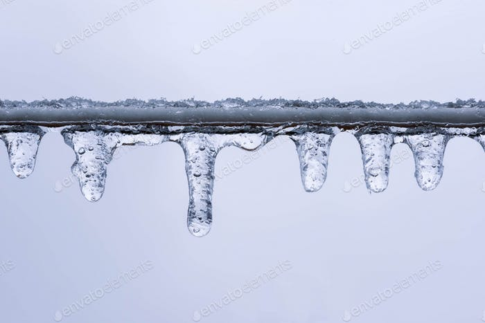 Closeup of tiny icicles on a clothesline in winter