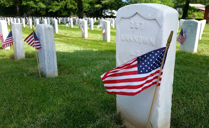 Graves of unknown soldiers in a Veteran's cemetery decorated with American flags