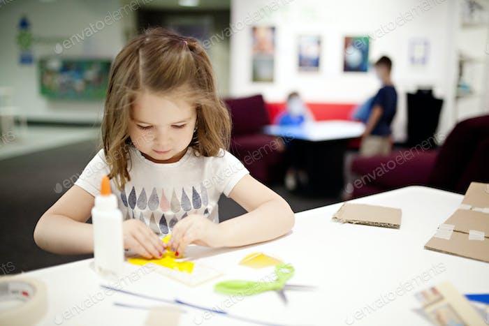 Mädchen arbeitet an einem Kunst- und Handwerksbauprojekt