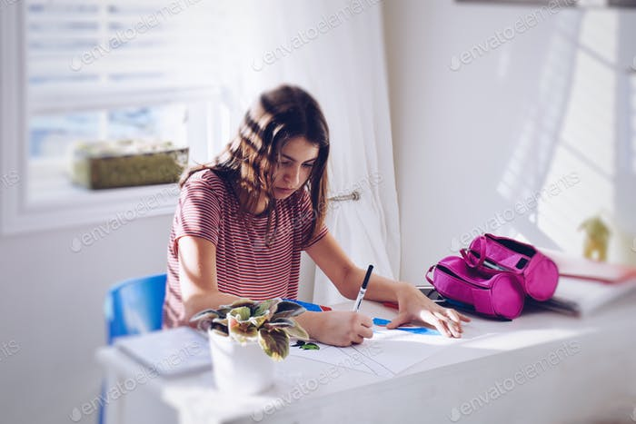 Young teenage girl working on her school project in a brightly lit room