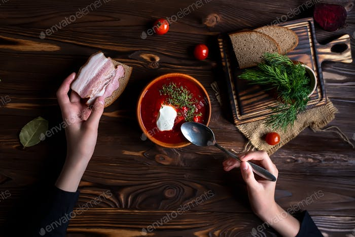 Ukrainian borscht in a plate next to the ingredients for soup. Hands holding sandwich with bacon