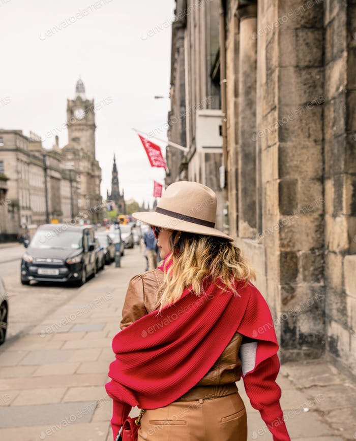 Woman walking down the street wearing a brown trilby hat and red scarf