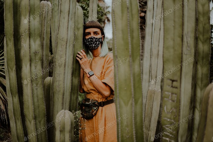girl wearing a yellow dress walking through the cacti during covid wearing a mask