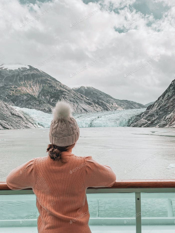 Girl on a cruise ship looking out at an Alaskan glacier.