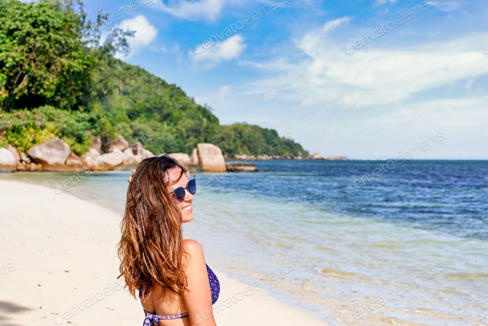 Young woman in bikini on tropical sandy beach, vacatio, summer, positive emotion.