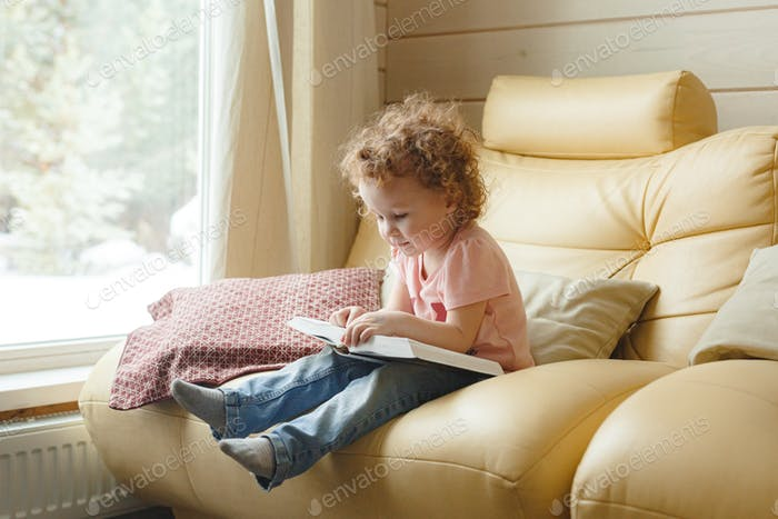 Little curly girl reading a book in living room