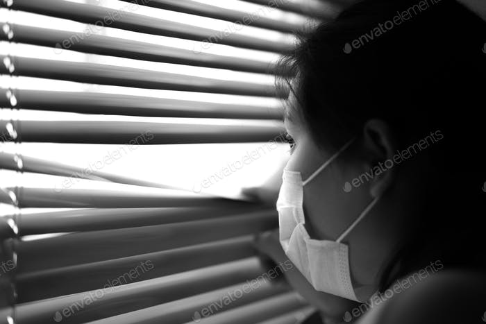 Portrait of a young girl wearing a disposable medical mask looking through blinders on a windows