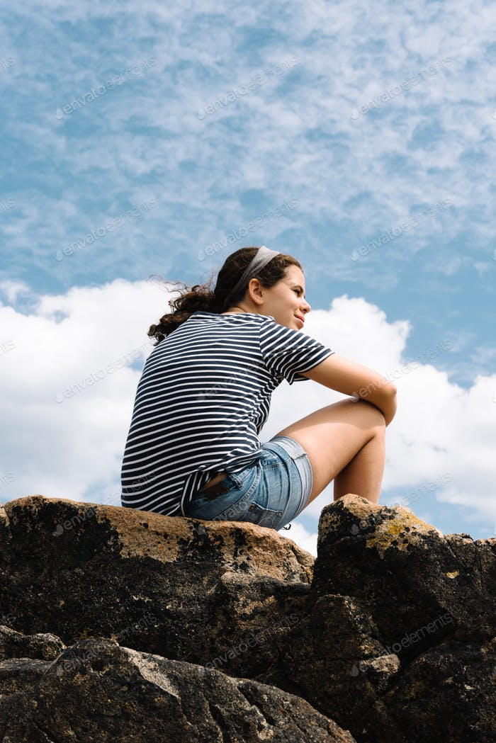 Happy young woman sitting on top of rock formation looking at the coastline. Landscape with girl in
