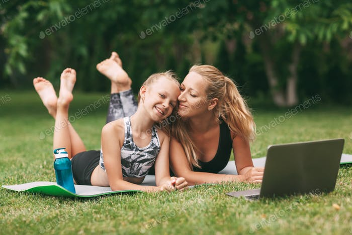 Mother and daughter practice online outdoors near their home during quarantine self-isolation during