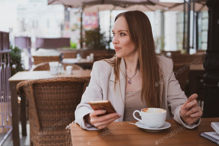 beautiful young woman with long hair is sitting in a street cafe and communicates using a smartphone