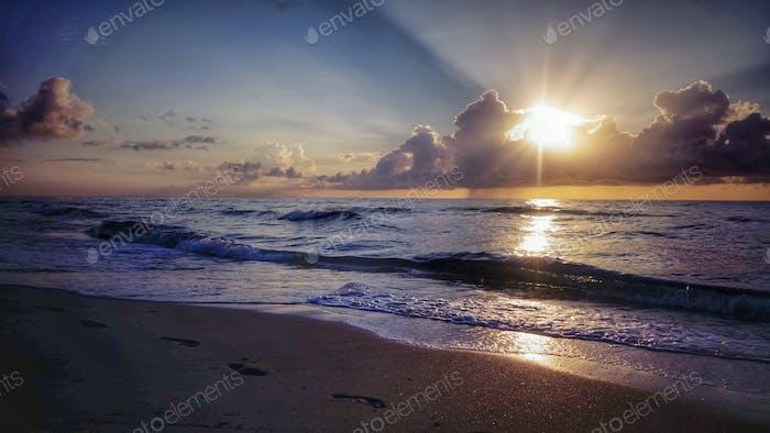 Sol mirando desde detrás de las nubes de la mañana sobre el océano