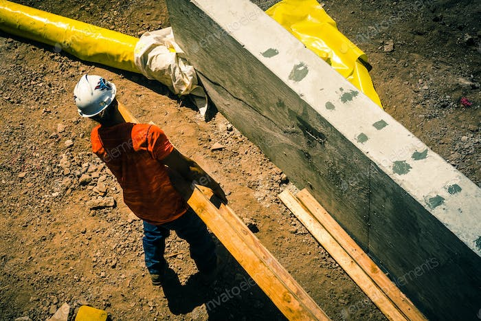 construction site with worker carrying lumber