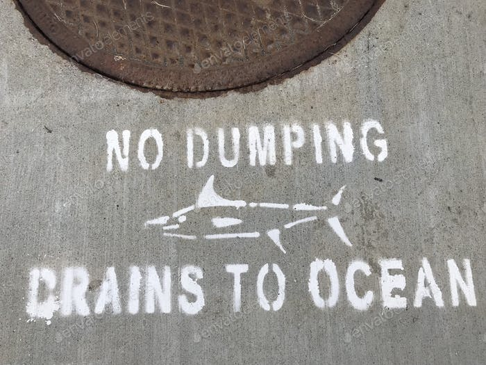A sign on the sidewalk says no dumping, drains to ocean to protect the fish and our oceans