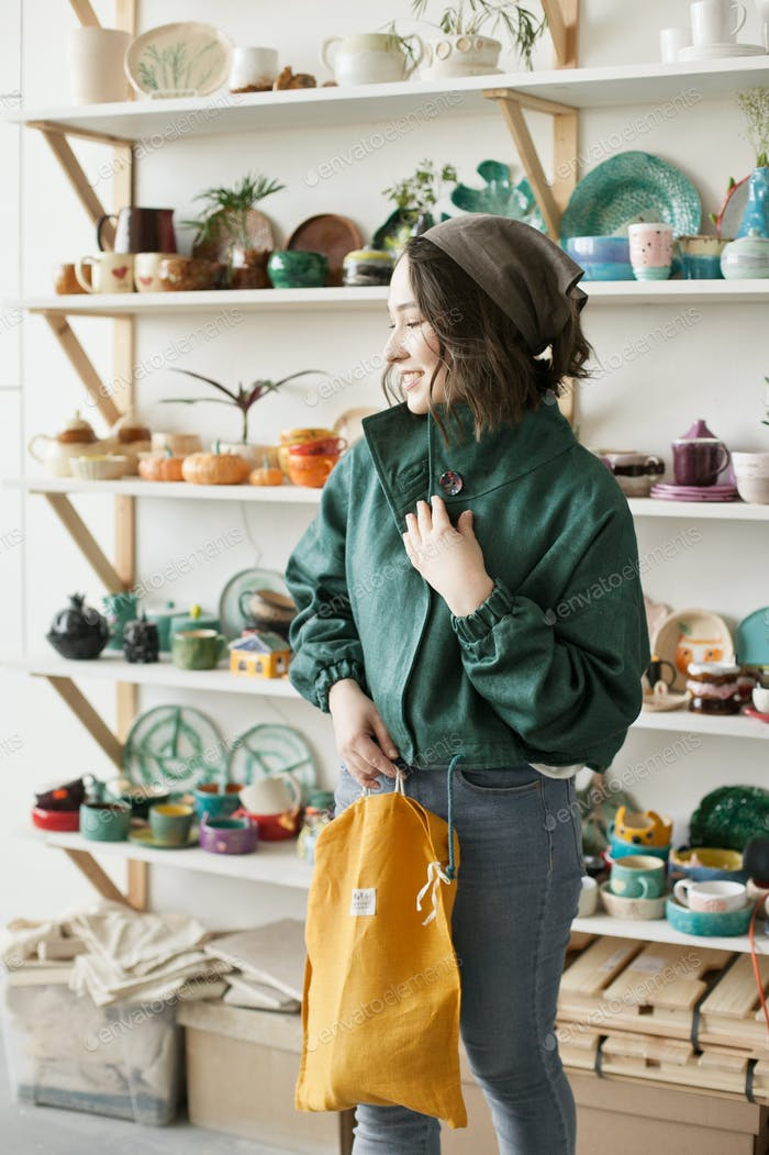 A young woman inside artisanal pottery shop wearing linen green jacket, eco conscious