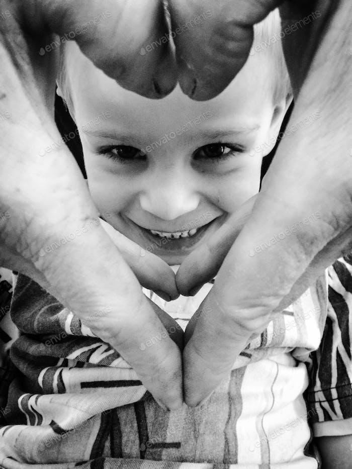 Junge in einem Herzen aus den Finger seines Vaters