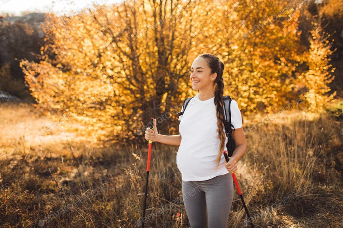 Pregnant woman nordic walking in autumn forest with backpack and trekking sticks. Healthy and active