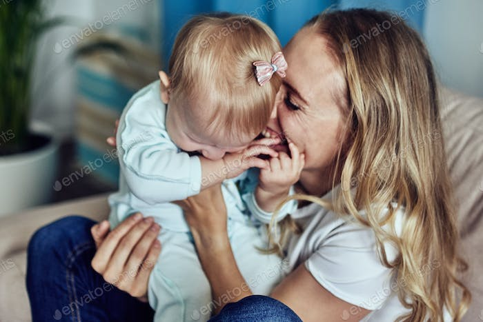 Mom and 1-year-old daughter spend time together at home.