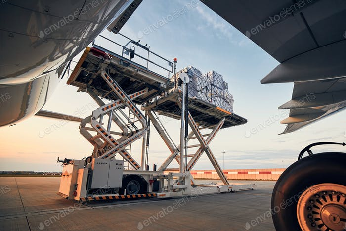 Preparation before flight. Loading of cargo containers to airplane at airport.