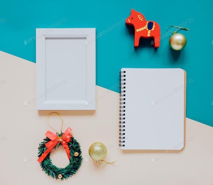 Kreativer flacher Bastel- und Fotorahmen, leeres Notizbuch mit Weihnachtsschmuck und Geschenk