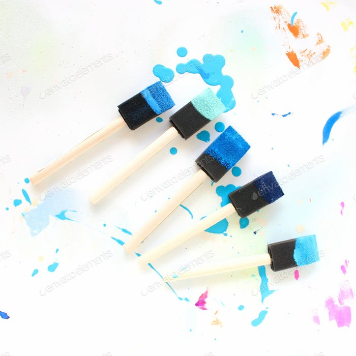 Foam paint brushes dipped in blue paint on a white background with hints of pink.