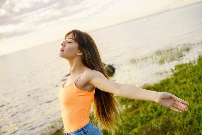 young attractive woman of Caucasian ethnicity on the shore of the lake with arms outstretched